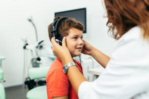 Jongetje met koptelefoon tijdens een gehoortest.